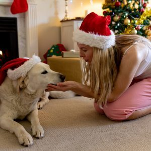 Image: dog and owner in front of Christmas tree.