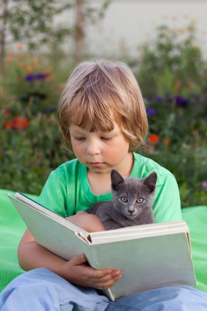Boy reading with a cat